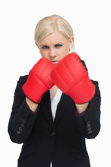 Serious businesswoman wearing red boxing gloves