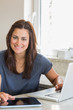 Smiling brunette using the tablet pc and laptop