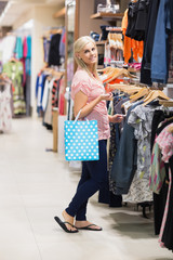 Woman is holding a bag smiling