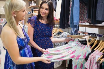 Two women talking beside clothes rail