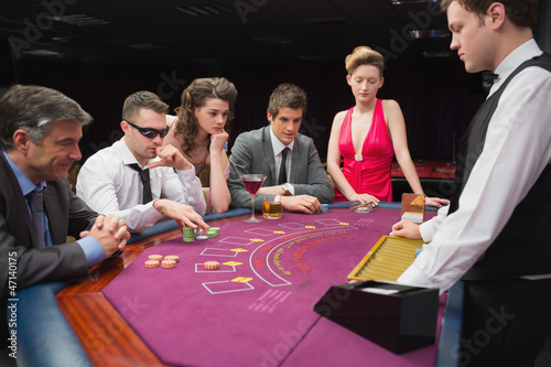 People sitting at table playing poker