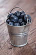 Blueberries in a bucket on wood