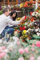 Couple looking through flowers