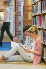 Boy and girl sitting on floor of library studying