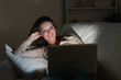 Woman lying on sofa with her laptop in night