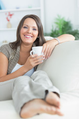 Happy woman drinking a mug on the sofa