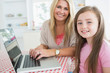 Woman typing at the laptop with daughter
