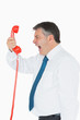 Businessman screaming directly into the handset