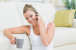 Cheerful woman drinking coffee while calling