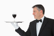 Happy waiter holding a glass of wine on a silver tray