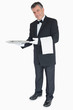 Waiter standing against the white background holding silver tray