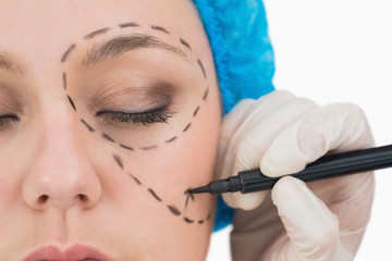Surgeon writing on the serious woman's face