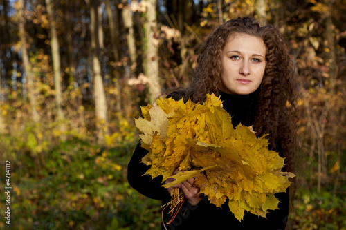 beautiful girl with leaves in autumn park