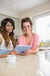 Happy girls with tablet computer having coffee