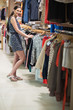 Woman is standing at the clothes rack and smiling