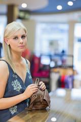 Woman holding handbag at counter