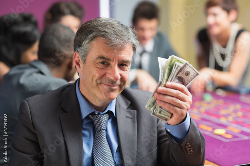 Man holding up money at roulette table