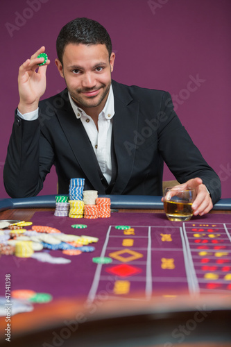 Man holding a chip and a glass of whiskey