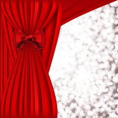 Holiday background with red satin and blurred lights.