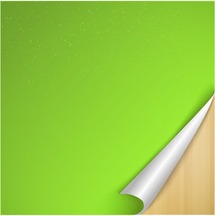 Sheet of Green Paper with Curved Corner on wooden background