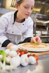Chef putting basil leaf on pizza