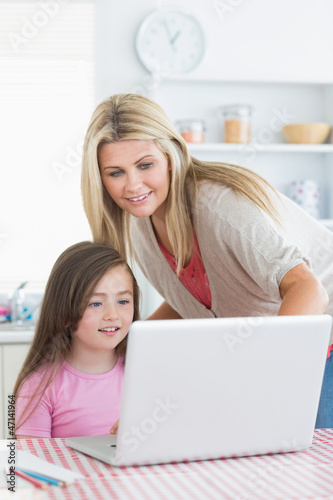 Woman and girl standing and sitting looking at laptop
