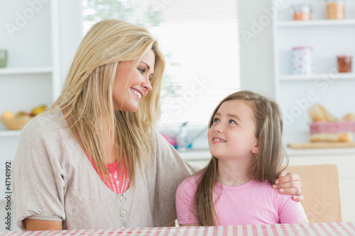 Mother and child looking at each other in kitchen