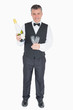 Smiling waiter holding glasses and champagne bottle