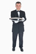 Waiter holding out empty silver tray