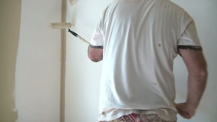 Man Rolling Paint onto Wall