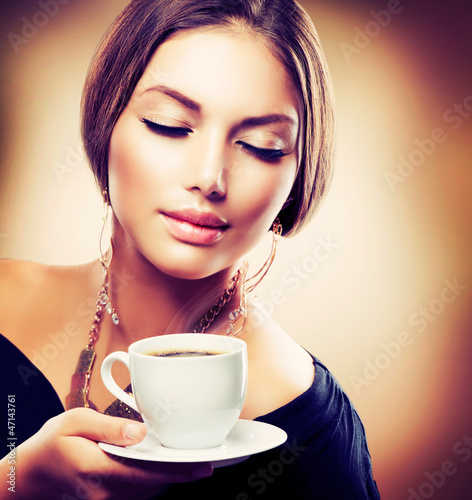 Beautiful Girl Drinking Tea or Coffee. Sepia Toned