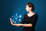 Young woman looking at modern tablet with abstract lights and so