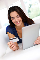 Brunette girl doing online shopping with digital tablet