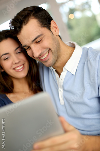 Smiling couple websurfing on internet with tablet