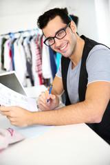 Smiling fashion designer in workshop