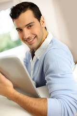 Young man with tablet sitting in sofa