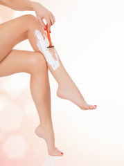Woman shaving her legs, abstract blurred background