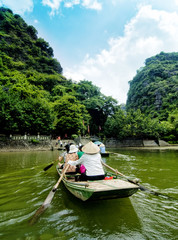woman climbing boat taking tourists to visit, trangan, ninhbinh,