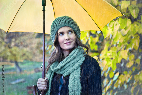 Woman with yellow umbrella smiling