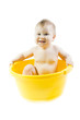 Cute baby taking bath in yellow tub