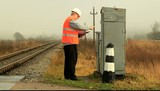 Railroad employee writes near the electrical enclosure poster