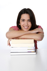 Portrait of cheerful student girl leaning on pile of books