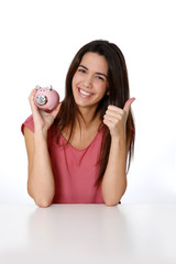 Girl holding piggy bank and showing thumb up