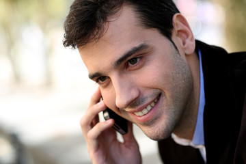 Young man in town talking on mobile phone