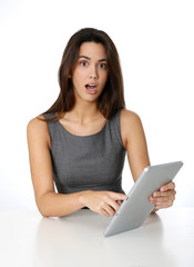 Young woman with surprised look in front of tablet