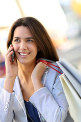 Attractive shopping girl in town talking on the phone