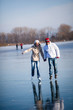 Couple ice skating outdoors on a pond on a lovely sunny winter d