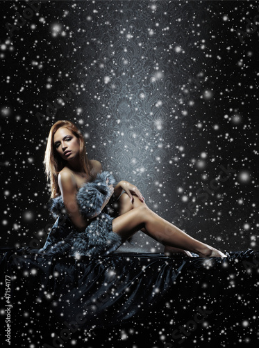 A young naked redhead woman in fur on a snowy background