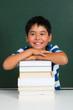 glücklicher grundschüler mit bücherstapel