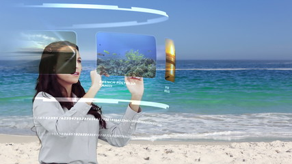 Woman looking at holiday on interactive media library on beach